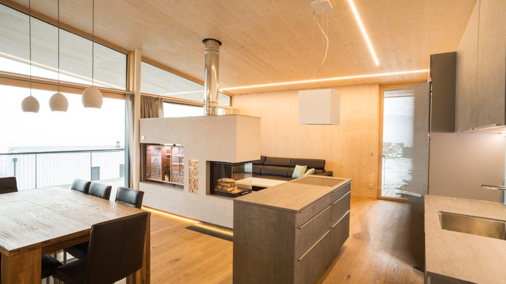 Der gemütliche, offene Wohnraum mit integrierter Küche, zentralem Esstisch und stylischem Kamin bekommt durch die natürlichen Massivholzwände in Sichtqualität ein besonderes Wohlfühlklima.