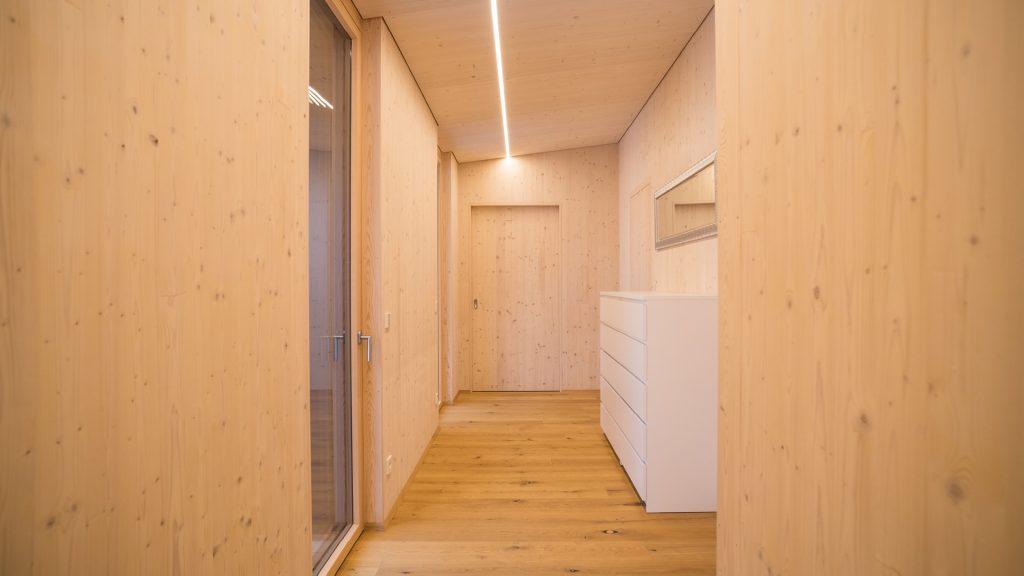 Massivholzwände in Sichtqualität verbreiten ein natürliches Wohlfühlklima in den Räumen