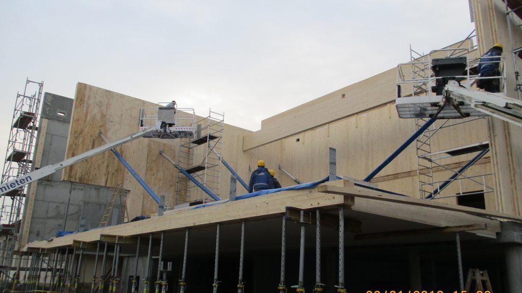 Mittels Hebebeühnen wird die Montagearbeit an den großformatigen Massivholz-Bauelementen erleichtert.