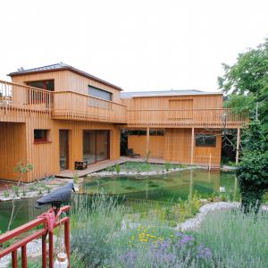 Massivholzhaus in schönster Architektur umgeben vom Schwimmteich