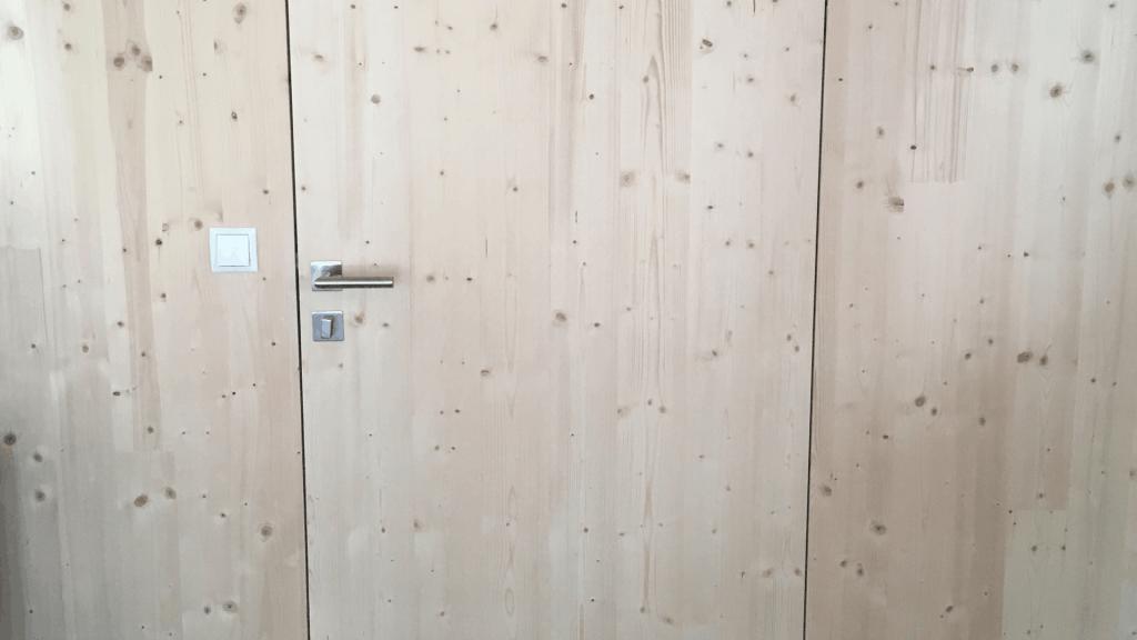 Formschön und Bündig. Wenn die Tür in der Massivholzwand verschwindet.