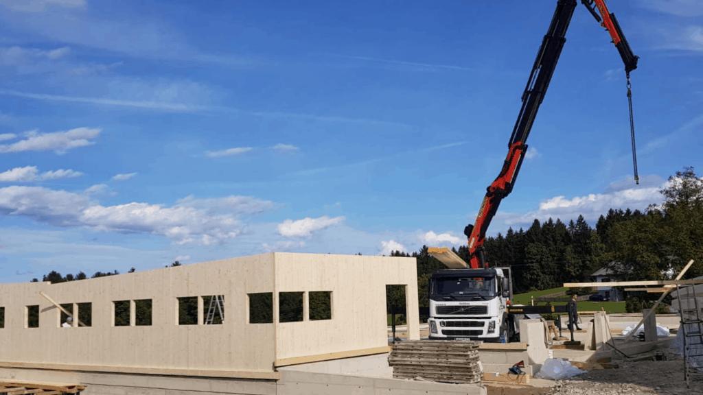 CLT Wände werden einfach mit dem Hebekran auf der Baustelle an Ort und Stelle gehoben und montiert.