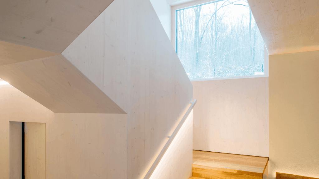 Das Haus Waldtraut wurde als Split-Level-Haus konzipiert und bietet damit auf 60 Quadratmeter Wohnraum für eine 4 köpfige Familie. Die Wände wurden in Wohnsichtqualität (weiß lasiertes CLT) ausgeführt.