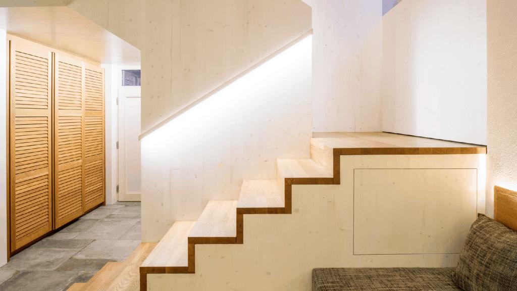 Jede Nische wurde sinnvoll genutzt. Auch der Platz unter den Stufen bietet Stauraum. Die beleuchteten Handläufe rücken die Massivholz-Wände ins rechte Licht.