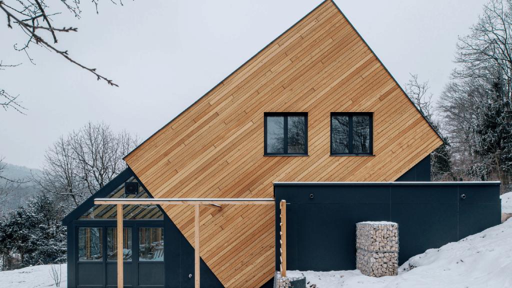 Das Haus Waldtraut liegt wie ein Würfel in der Landschaft und fängt durch seine außergewöhnliche Form das Sonnenlicht perfekt ein. Auch die Fassade wurde mit natürlichem Holz gestaltet.